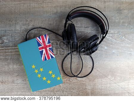 Headphones And Book. The Book Has A Cover In The Form Of Tuvalu Flag. Concept Audiobooks. Learning L