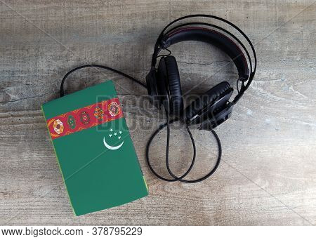 Headphones And Book. The Book Has A Cover In The Form Of Turkmenistan Flag. Concept Audiobooks. Lear