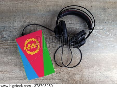 Headphones And Book. The Book Has A Cover In The Form Of Eritrea Flag. Concept Audiobooks. Learning