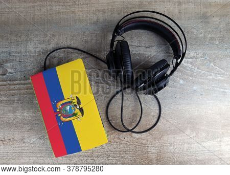 Headphones And Book. The Book Has A Cover In The Form Of Ecuador Flag. Concept Audiobooks. Learning