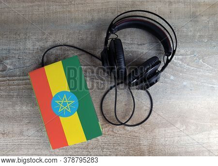 Headphones And Book. The Book Has A Cover In The Form Of Ethiopia Flag. Concept Audiobooks. Learning