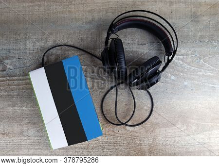 Headphones And Book. The Book Has A Cover In The Form Of Estonia Flag. Concept Audiobooks. Learning
