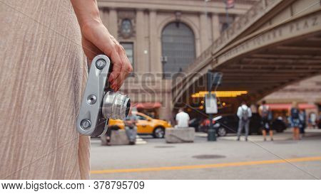 Young girl with a retro camera at the railway station in New York, close-up. USA, NYC 2019