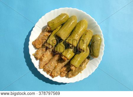 Traditional Stuffed Squash And Cabbage Rolls On White Plate On Blue Bright Background. Famous Tradit