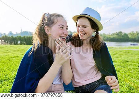 Girlfriends Teenagers Having Fun While Sitting On The Grass On A Sunny Summer Day, Friendship Adoles