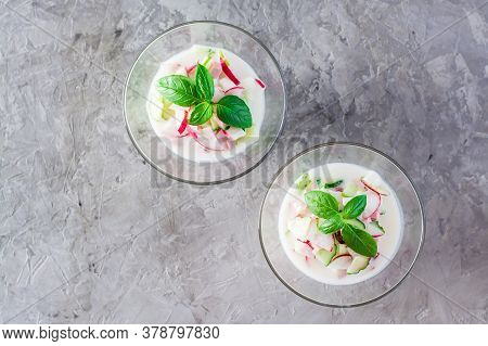 Russian Kitchen. Okroshka - Cold Soup With Vegetables, Sausages And Herbs On Kefir In Glass Bowls. T