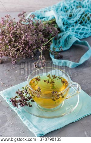 Alternative Medicine. A Cup Of Tea With Oregano  On The Table And A Dry Bunch Of Herbs Nearby