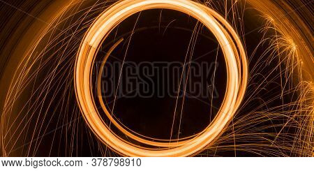 Shiny Sparks In The Shape Of A Circle, Scattering Sparks On On A Black Background. Long Exposure.