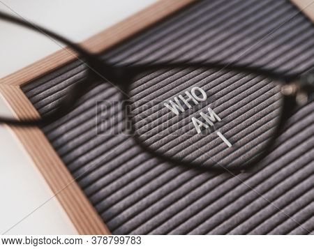 Top View On Letterboard With Words Who Am I Through Eyeglasses. Flat Lay Concept Of Psychological Se