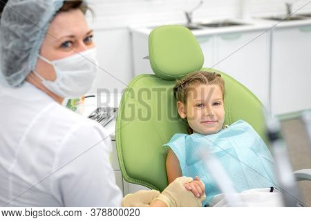 Happy Caucasian Kid On Regular Check Up Of Teeth In Dental Clinic. Dentist Holds A Seven Year Old Gi