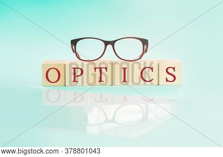 Eyeglasses On Top Of Word Optics On Mint. Glasses Or Spectacles Reflected On Mint Background. Optics