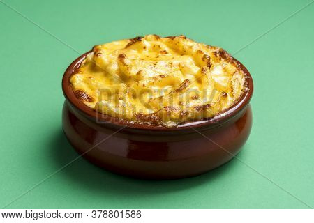 Cheese Macaroni In A Ceramic Tray Isolated On A Green Colored Background. Cooked Mac And Cheese With