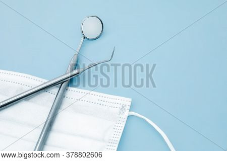 Medical Mask And A Set Of Metal Dental Instruments For Dental Care On A Blue Background. Selective F