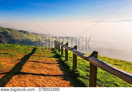 Picturesque Green Hills, Pasture And Hiking Trail With Wooden Fence In Sunlight. Scenic Countryside