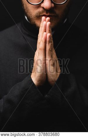 Partial View Of Bearded Priest With Praying Hands Isolated On Black