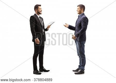 Full length profile shot of two male colleagues talking isolated on white background