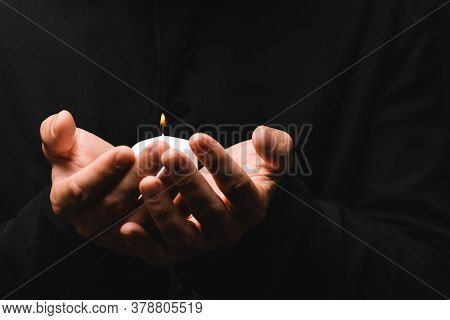 Partial View Of Priest Holding Burning Candle Isolated On Black