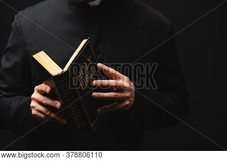 Partial View Of Pastor Holding Holy Bible In Hands Isolated On Black