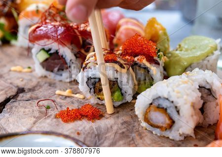 Japanese Food, Eating Fresh Sushi Or Sashimi Made From Rice With Salmon, Avocado, Cucumber, Red Fish
