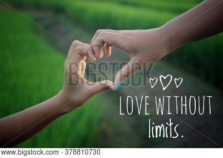 Inspirational Quote - Love Without Limits. With Hands Making Love Sign In The Field On Green Paddy P