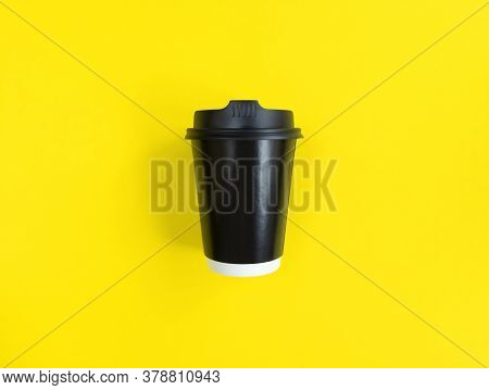 Black Paper Coffee Cup To Go On Yellow Backgroud. Flat Lay Style. Minimal Concept. Stock Photo.