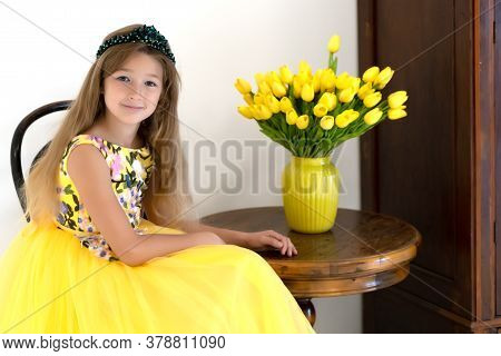 A Cute Little Girl With A Bouquet Of Tulips, In The Spring In The Studio. The Concept Of The Awakeni