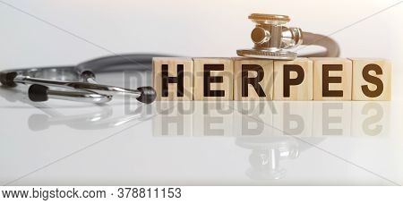 Herpes The Word On Wooden Cubes, Cubes Stand On A Reflective White Surface, On Cubes - A Stethoscope