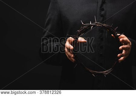 Cropped View Of Pastor Holding Wreath With Spikes In Hands Isolated On Black