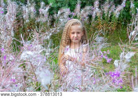 A Little Blonde Girl Of 5-6 Years Old In A White Sundress Stands Surrounded By Blooming Sally, Firew