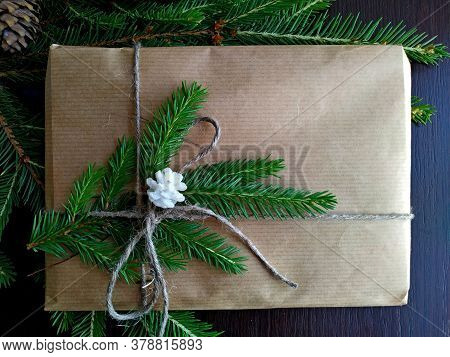 A Christmas Gift Wrapped In Craft Paper And Tied With Linen Thread On Fir Branches With Fir-cone