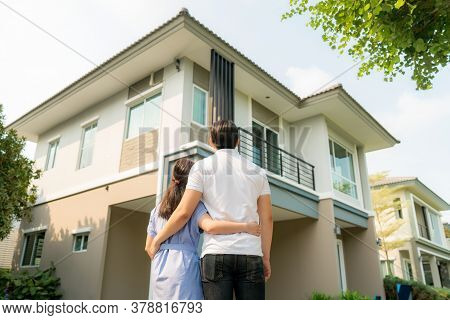 Back Portrait Of Asian Young Couple Standing And Hugging Together Looking Happy In Front Of Their Ne