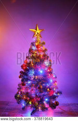 Christmas tree with festive lights, purple background