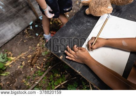 Partial View Of African American Child Holding Pencil While Writing Near Kid