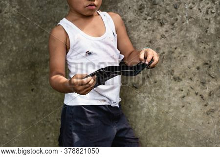 Cropped View Of Beggar African American Child Holding Wallet Near Concrete Wall On Urban Street