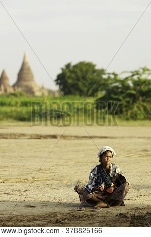 Bagan/myanmar-october4th 2019: A Native Burmese Woman Is Carrying A Baby Asking For Money From A Tou
