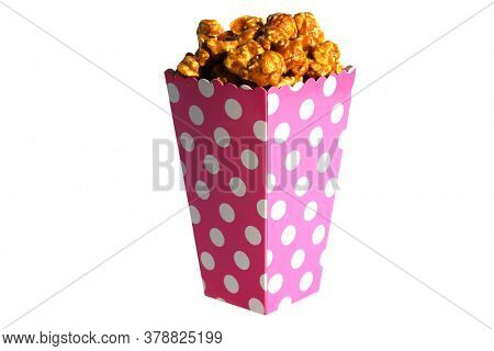 Popcorn. Caramel flavored Pop Corn in a Pink with White Dots Paper Container. Isolated on white. Room for text. Clipping Path. Caramel Popcorn is enjoyed by happy people world wide.