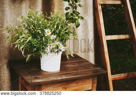 A Bouquet Of Wildflowers And Chamomiles On A Wooden Table. Flowers On A Wooden Table, Rustic Bouquet