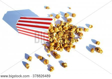 Popcorn. Caramel flavored Pop Corn in a Red and White Striped Paper Container. Isolated on white. Room for text. Clipping Path. Caramel Popcorn is enjoyed by happy people world wide.