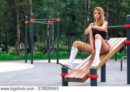 Young Sportswoman Sitting On Wooden Press Bench