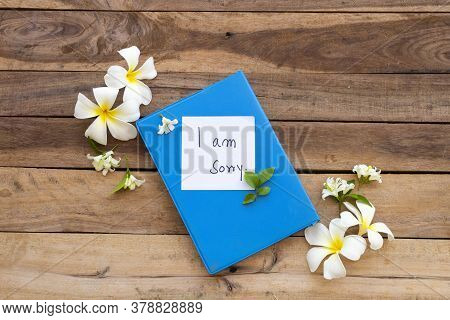 I Am Sorry Message Card Handwriting On Blue Diary Book With White Flowers Frangipani ,jasmine Arrang