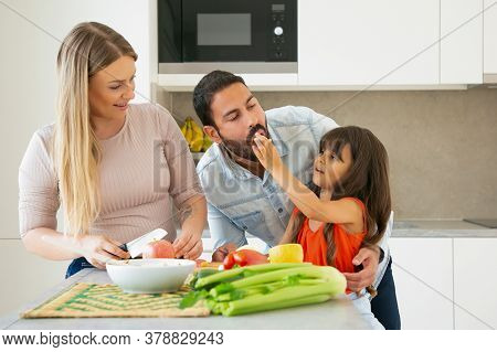 Family Cooking And Eating At Home During Pandemic. Girl Giving Slice Of Veg To Dad For Taste While M