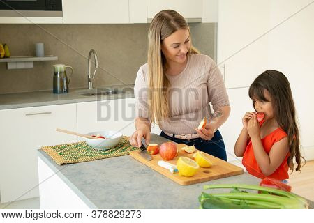 Mom Giving Daughter To Taste Apple Slice While Cooking Salad. Girl And Her Mother Cooking Together,