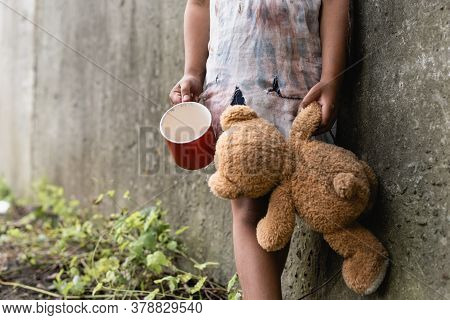 Cropped View Of Beggar African American Child Holding Teddy Bear And Cup Near Concrete Wall On Urban
