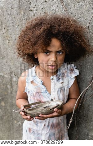 Beggar African American Child Looking At Camera While Holding Dirty Plate And Spoon Near Concrete Wa