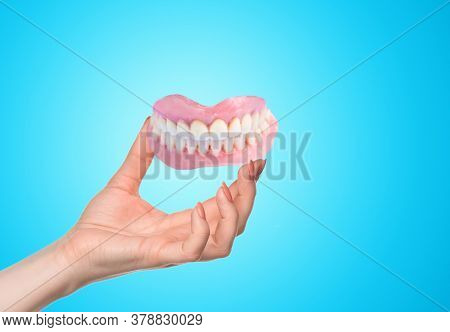Female Hand And False Prosthese. Dental Hygienist Checkup Concept. Full Removable Plastic Denture Of