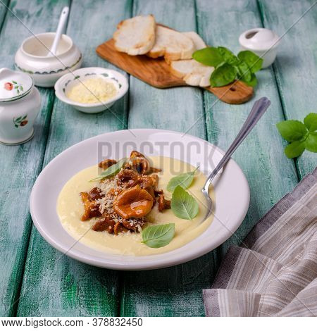 Traditional Polenta With Mushrooms And Cheese In A Dish On A Green Wooden Background. Selective Focu