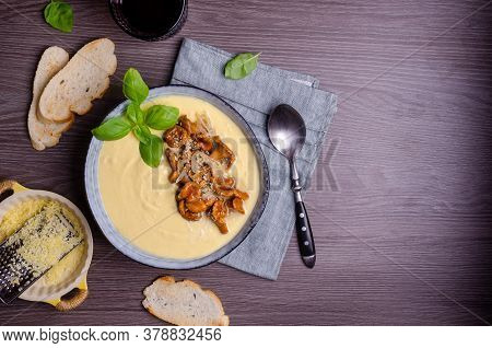 Traditional Polenta With Mushrooms And Cheese In A Dish On A Dark Wooden Background. Selective Focus