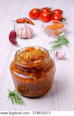 Canned Cauliflower With Vegetables In Tomato Sauce In A Jar On A Light Wooden Background. Selective