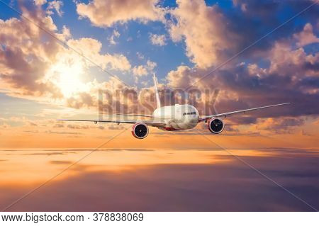 Jet Passenger Plane Flies At Sunset In The Clouds