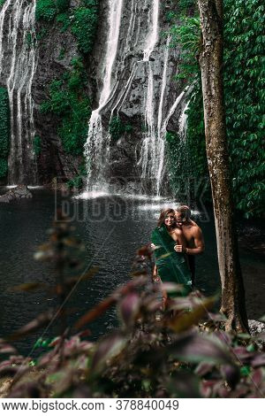 Lovers At The Waterfall. Beautiful Couple At A Waterfall In Indonesia. A Couple In Love Travels Arou